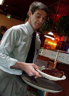 Sam serving platters of ribs.