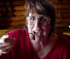 Peg dips pork into the barbeque sauce and not on her blouse.